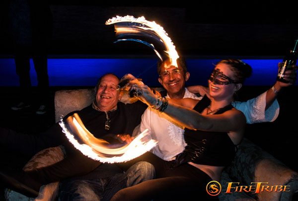 Guests pose alongside the fire dancers at a Burning Booth session with FireTribe