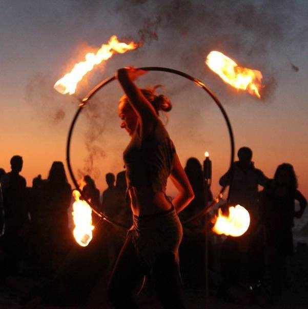 sandy dances with her fire hoop at the clifton fire jam in cape town