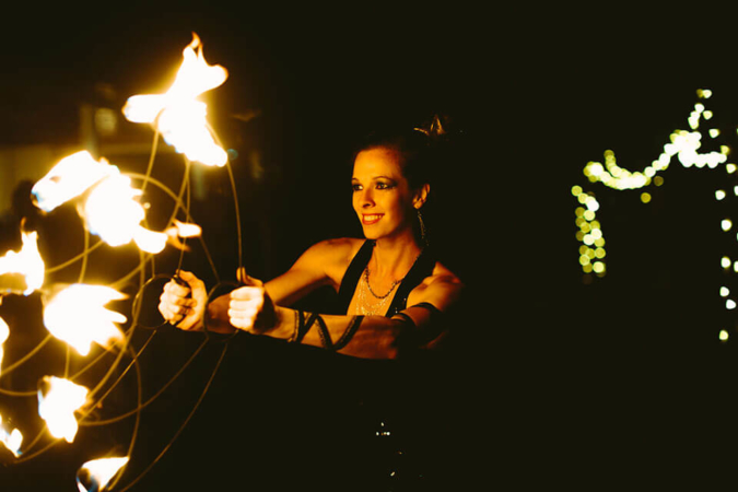 A photo by Tabitha Mae of Caitlin Louise entertaining guests with fire dancing at Lourensford wedding using protea fire fans made by FireTribe