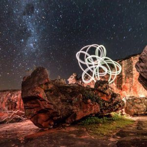 long exposure photo of the night sky in the cederburg with a pod poi making light trails on a boulder