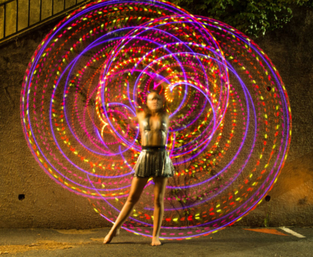 a dancer twirls an led hula hoop with pink lights