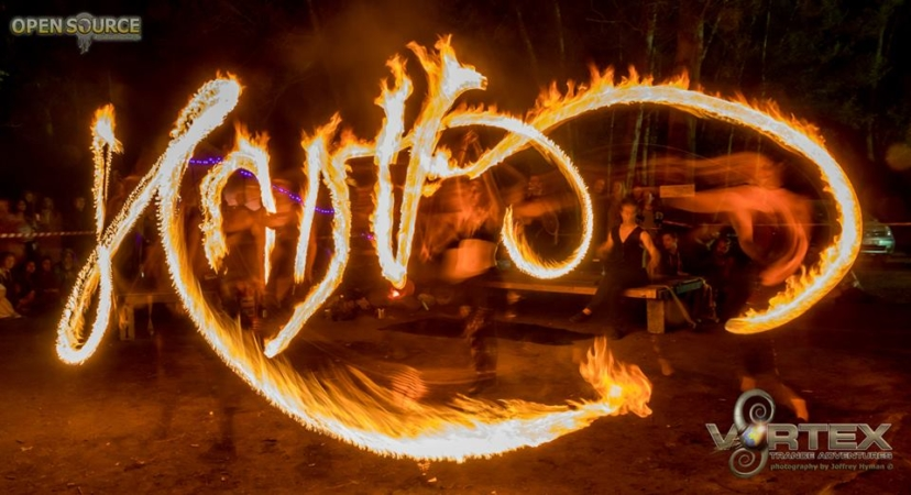 A FireTribe dancer uses fire to light paint the word Vortex in this long exposure festival photograph