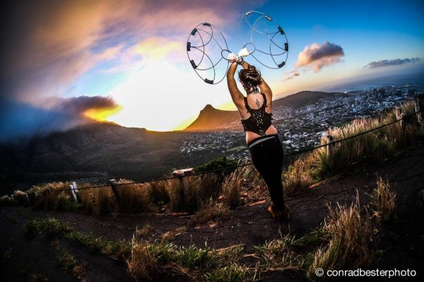 Conrad Bester photograph of Ashley wedlake posing at sunset with firetribe's closed protea fire fans
